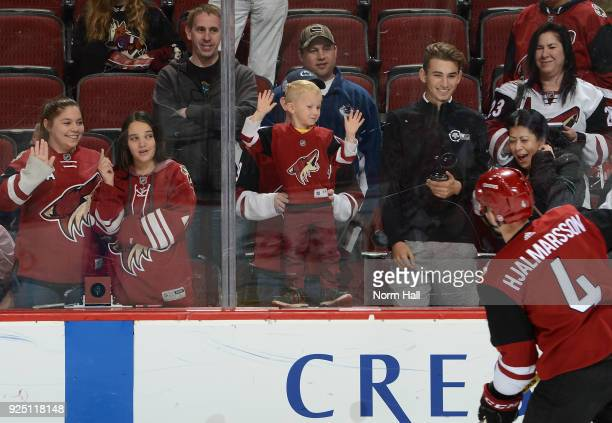 Fans watch Niklas Hjalmarsson of the Arizona Coyotes during warmups prior to a game against the Vancouver Canucks at Gila River Arena on February 25...