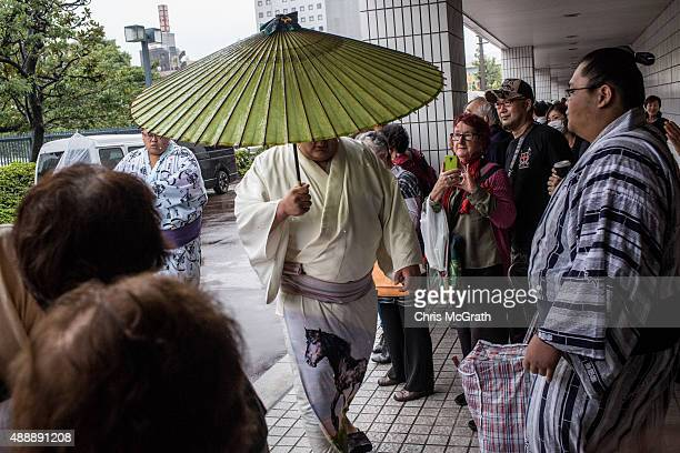 Fans watch on as a sumo wrestler arrives for his fight during the Tokyo Grand Sumo tournament at the Ryogoku Kokugikan on September 17 2015 in Tokyo...