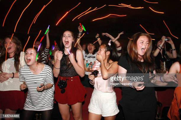 Fans watch One Direction perform live on stage at St James Theatre on April 22 2012 in Wellington New Zealand