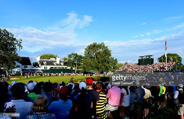 Fans watch play on the 18th green as Justin Rose of England reacts after putting on the 18th hole to complete the final round of the 113th U.S. Open...