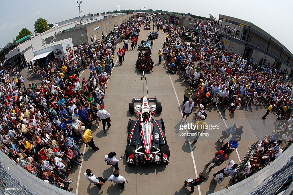 Fans watch pole sitter Ryan Briscoe's #2 IZOD Team Penske Chevy Dallara DW12 roll through Gasoline Alley after practice for the the 96th Indianapolis 500 Mile Race at the Indianapolis Motor Speedway on May 25, 2012 in Indianapolis, Indiana.