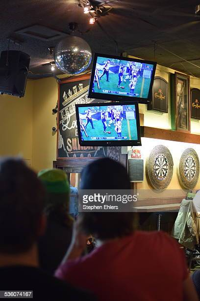 Fans watch Super Bowl XLIX on wall mounted televisions at a sports bar in Whistler Canada