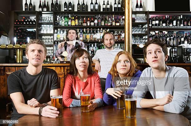 fans watch television football in a pub bar