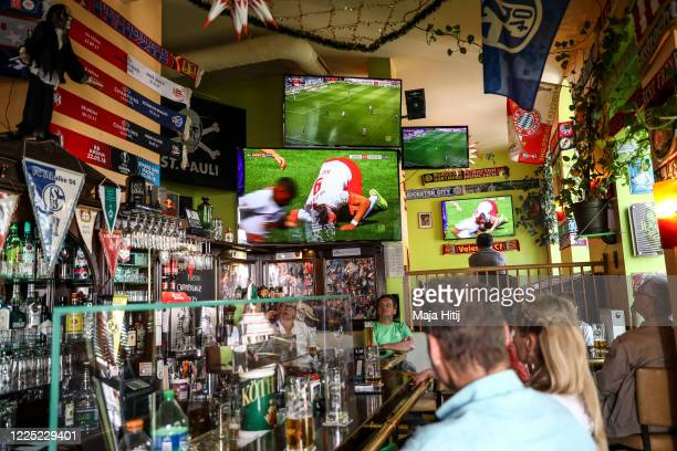 Fans watch the Bundesliga matches in a bar outside the Red Bull Arena during the Bundesliga match between RB Leipzig and SportingClub Freiburg on May...