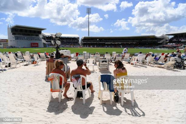 Fans watch the cricket from the beach area during Day One of the First Test match between England and West Indies at Kensington Oval on January 23...