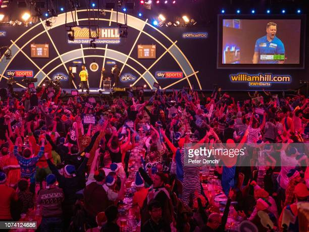 Fans watch the darts action in the arena at Alexandra Palace on December 16, 2018 in London, England.