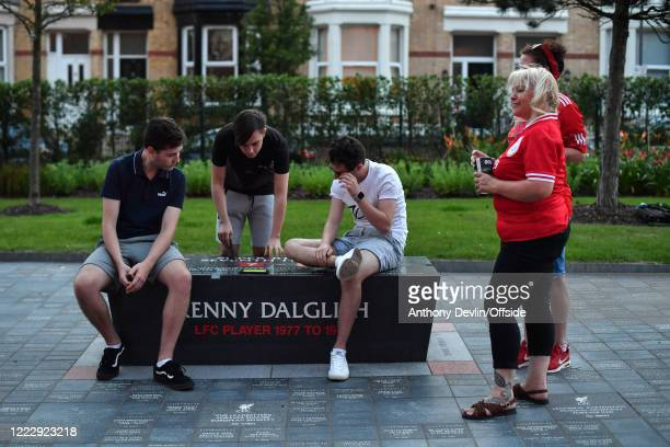 Fans watch the final minutes of the Chelsea v Man City match on a structure outside Anfield dedicated to Kenny Dalglish on June 25 2020 in Liverpool...