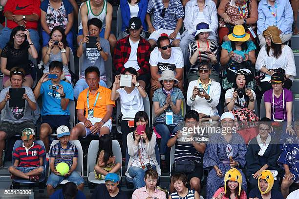 Fans watch the first round match between Phillip Kohlschreiber of Gemany and Kei Nishikori of Japan during day one of the 2016 Australian Open at...