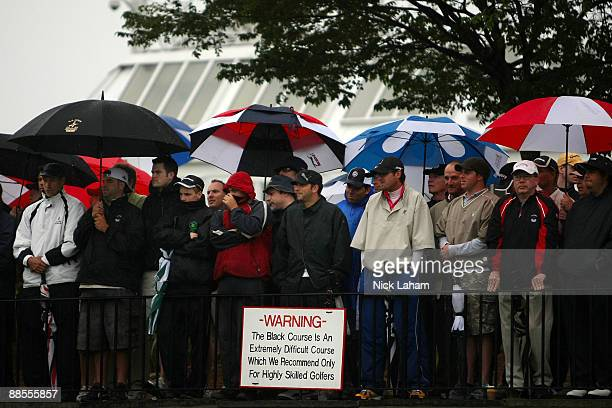 Fans watch the first tee ball of the championship in the rain during the first round of the 109th US Open on the Black Course at Bethpage State Park...
