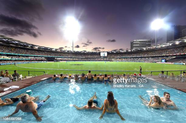 Fans watch the game from the pool during the Big Bash League match between the Brisbane Heat and the Adelaide Strikers at The Gabba on December 19,...