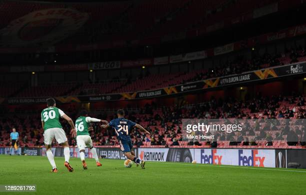 Fans watch the game while abiding to social distancing rules during the UEFA Europa League Group B stage match between Arsenal FC and Rapid Wien at...