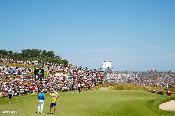 Fans watch the group of Rory McIlroy of Northern Ireland and Jordan Spieth and Zach Johnson of the United States on the first green during the first...