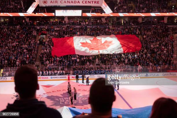 Fans watch the lights show and other fans passing by hand overhead the Canadian Flag and the Leafs Team Flag during the playing of the National...