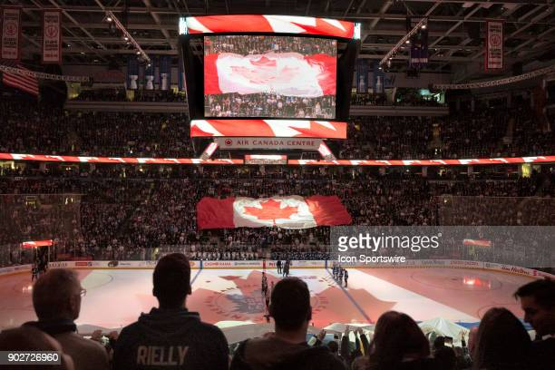 Fans watch the lights show and other fans passing by hand overhead the Canadian Flag and the Leafs Team Flag before the regular season NHL game...