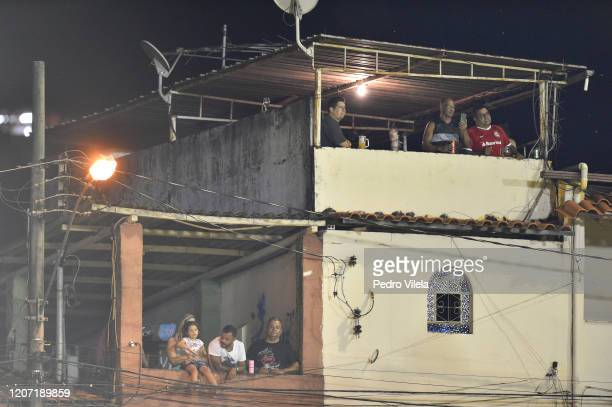 Fans watch the march from neighbouring houses during the match between Villa Nova and Atletico MG as part of the Minas Gerais State Championship 2020...