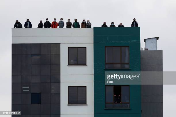 Fans watch the match between Bolivia and Argentina from a building next to Estadio Hernando Siles on October 13, 2020 in Miraflores, La Paz, Bolivia....