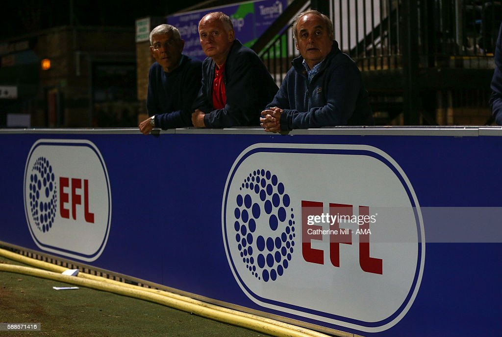 Fans watch the match from behind an EFL advertisement board during the EFL Cup match between Wycombe Wanderers and Bristol City at Adams Park on August 8, 2016 in High Wycombe, England.