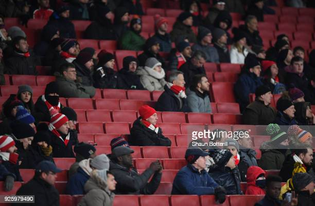 Fans watch the match with empty seats all around during the Premier League match between Arsenal and Manchester City at Emirates Stadium on March 1...