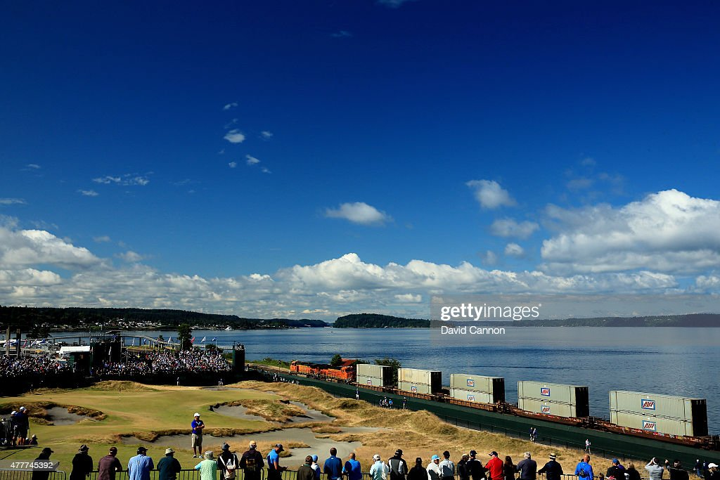 Fans watch the play on the 17th hole as a train passes by during the first round of the 115th U.S. Open Championship at Chambers Bay on June 18, 2015 in University Place, Washington.