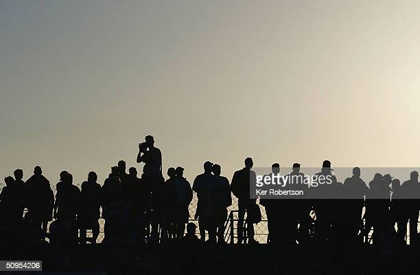 Fans watch the race continue into the night during the Le Mans 24 Hour race at the Circuit des 24 Hours du Mans on June 12, 2004 in Le Mans, France.