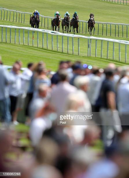 Fans watch the runners and riders in the Racing To School Novice Stakes at Haydock Park Racecourse on June 9, 2021 in Newton-le-Willows, England.
