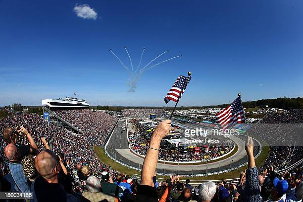 Fans wave American flags as five CJ6A's from Affordable Warbirds perform a flyover prior to the NASCAR Sprint Cup Series Goody's Headache Relief Shot...