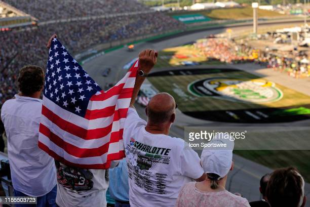 Fans wave an American Flag during the National Anthem before the start of the Monster Energy NASCAR Cup Series Quaker State 400 presented by Walmart...