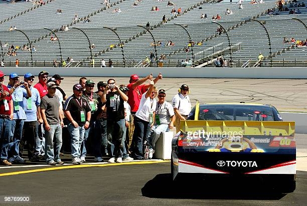 Fans wave as David Reutimann driver of the Aaron's Dream Machine Toyota pulls on to the track during practice for the CROWN ROYAL Presents the Heath...
