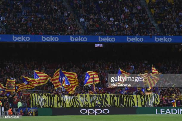 Fans wave flags and hold up a banner in support for Catalan independence during the Liga match between FC Barcelona and Real Valladolid CF at Camp...