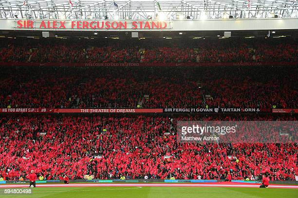 Fans wave flags at Old Trafford the home stadium of Manchester United with a banner celebrating Sir Alex Ferguson the head coach / manager of...