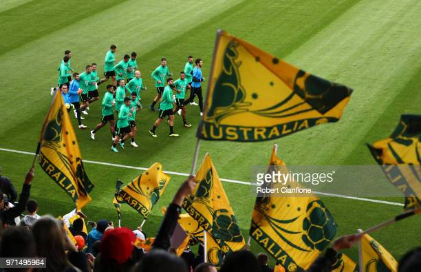 Fans wave flags in support as the Australia team warm up during an Australian Socceroos training session ahead of the FIFA World Cup 2018 in Russia...