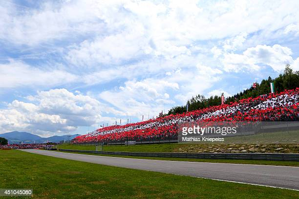 Fans wave flags in the stands before the Austrian Formula One Grand Prix at Red Bull Ring on June 22 2014 in Spielberg Austria