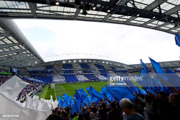Fans wave flags the teams enter the field before the Premier League match between Brighton and Hove Albion and Manchester City at Amex Stadium on...