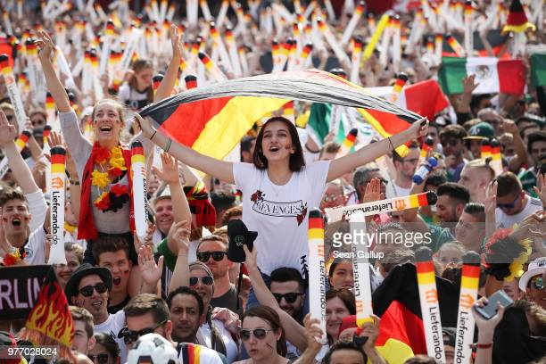 Fans wave German flags at the Fanmeile public viewing area prior to the Germany vs Mexico 2018 FIFA World Cup match on June 17 2018 in Berlin Germany...