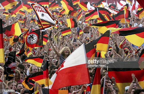 Fans wave German flags while watching the Group A match between Germany and Poland on a huge Television screen at the Fanfest on June 14 2006 in...