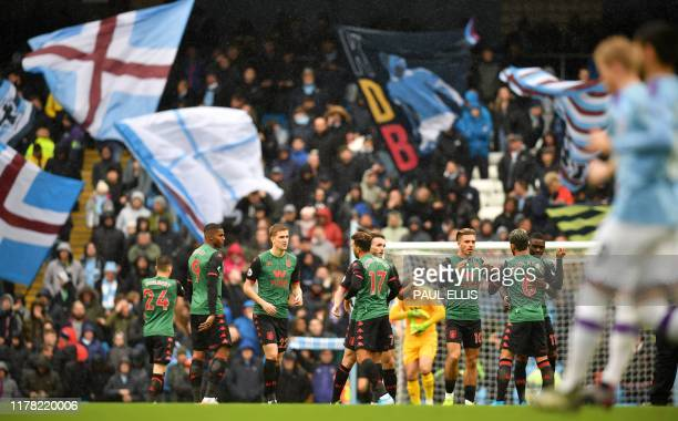 Fans wave giant flags as Aston Villa players warm up ahead of the English Premier League football match between Manchester City and Aston Villa at...