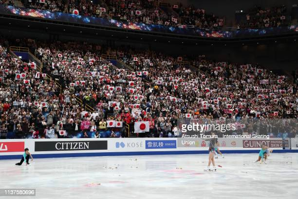 Fans wave national flags as RikaKihira of Japan applauds after competing in the Ladies Free Skating on day three of the 2019 ISU World Figure...