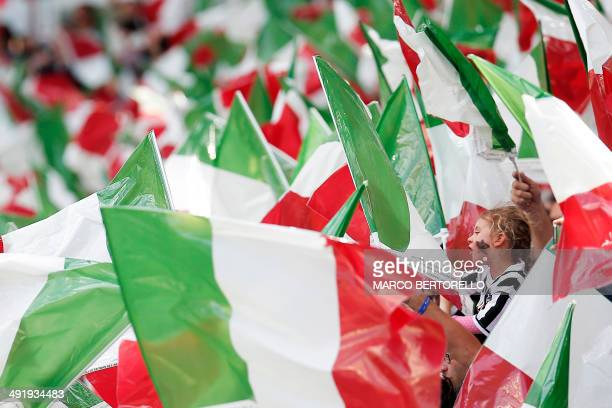 Fans wave Otalian flags during the Italian Serie A football match Juventus vs Cagliari on May 18 2014 at the Juventus Stadium in Turin Juventus won...