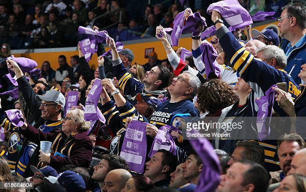 Fans wave purple towels displaying who they're fighting for on Hockey Fights Cancer Night during an NHL game between the Buffalo Sabres and the...