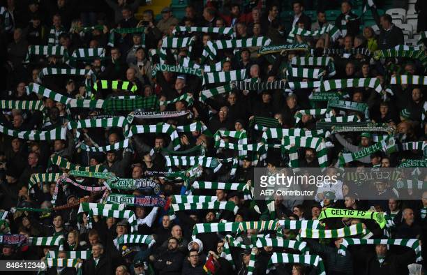 Fans wave scarves and flags during the UEFA Champions League Group B football match between Celtic and Paris SaintGermain at Celtic Park in Glasgow...