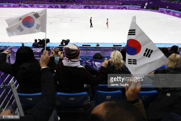 Fans wave South Korean flags as Kyueun Kim and Alex Kang Chan Kam of Korea prepare to begin the Pair Skating Short Program on day five of the...