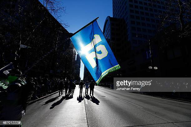 Fans wave the 12th Man flag to celebrate the Seattle Seahawks victory in Super Bowl XLVII during a parade on February 5 2014 in Seattle Washington