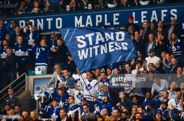 Fans wave the Stand Witness flag before while the Toronto Maple Leafs play the Boston Bruins in Game Six of the Eastern Conference First Round during...