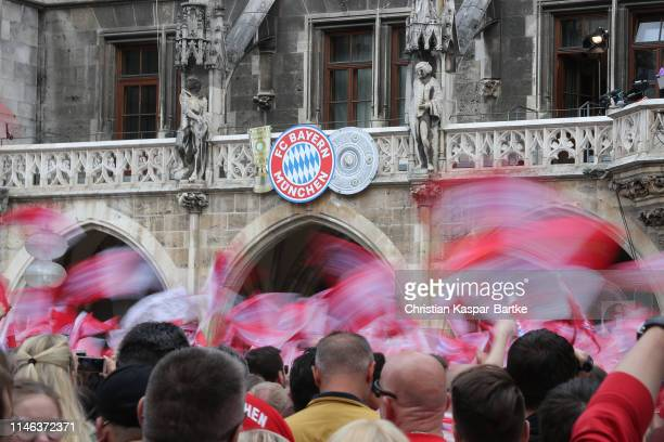 Fans wave their flags during an event to celebrate FC Bayern Muenchen winning the Bundesliga and the German Cup at at Marienplatz on May 26 2019 in...