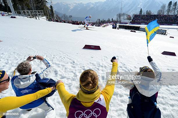 Fans wave with Swedish flag as Sweden's Marcus Hellner competes in the Men's CrossCountry Skiing 4 x 10km Relay at the Laura CrossCountry Ski and...
