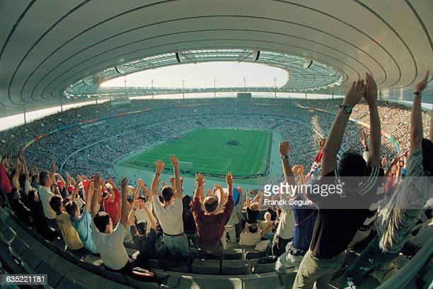 "Fans waving hands doing ""La Ola"" before a 1998 World Cup match at the Stade de France.   Location: Saint-Denis, France."