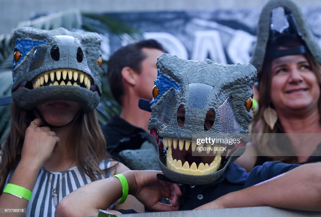Fans wear dinosaurs masks waiting for the premiere of 'Jurassic World: Fallen Kingdom' at The Walt Disney Concert Hall in Los Angeles, California on June 12, 2018.