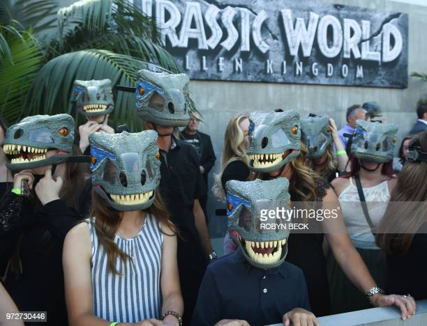 Fans wear dinosaurs masks waiting for the premiere of Jurassic World Fallen Kingdom at The Walt Disney Concert Hall in Los Angeles California on June...