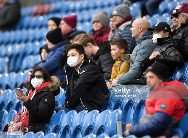 Fans wear disposable face masks prior to the Premier League match between Burnley FC and Tottenham Hotspur at Turf Moor on March 07, 2020 in Burnley,...