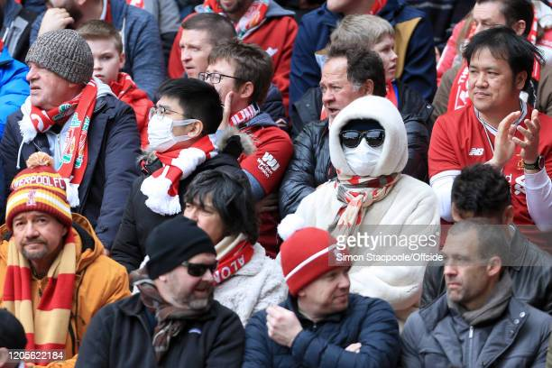 Fans wear facemasks due to Coronavirus concerns during the Premier League match between Liverpool FC and AFC Bournemouth at Anfield on March 7, 2020...